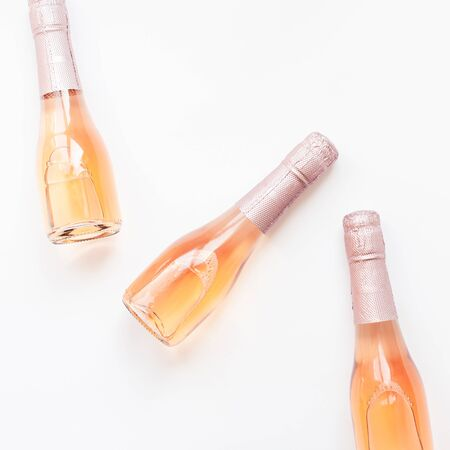 Bottles of rose champagne wine in minimal composition isolated on white background with copy space. Natural light. Template for tasting, degustation invitation card. Top view. Flat lay