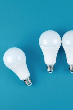 Energy-saving and eco-friendly life in conceptual frame pattern. Creative top view flat lay of LED light bulbs composition with copy space on blue background in minimal style.