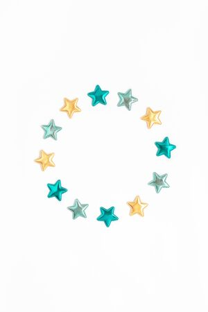 Holiday composition. New Year or Christmas pattern flat lay top view Xmas holiday celebration decorative color stars round wreath frame on white background with copy space. Template of greeting card