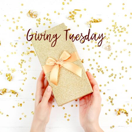 Giving Tuesday is a global day of charitable giving after Black Friday shopping day. Charity, give help, donations and support concept with text message sign. Gift box in woman hands, white background