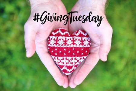 Giving Tuesday is a global day of charitable giving after Black Friday shopping day. Charity, give help, donations and support concept with text message sign and red knitted heart in man handful