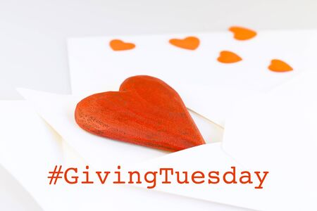 Giving Tuesday is a global day of charitable giving after Black Friday shopping day. Charity, give help, donations and support concept with text message sign and red wooden heart in envelope Foto de archivo