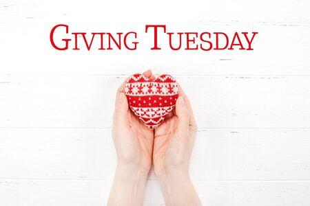 Giving Tuesday es un día mundial de donaciones caritativas después del día de compras del Black Friday. Caridad, dar ayuda, donaciones y concepto de apoyo con letrero de mensaje de texto y corazón de punto rojo en manos de mujer