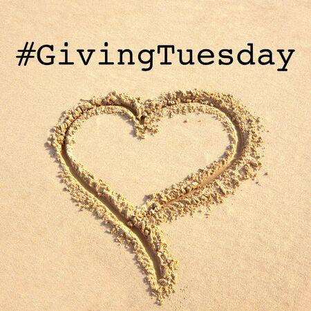 Giving Tuesday es un día mundial de donaciones caritativas después del día de compras del Black Friday. Caridad, dar ayuda, donaciones y concepto de apoyo con signo de mensaje de texto y corazón dibujado en la playa de arena
