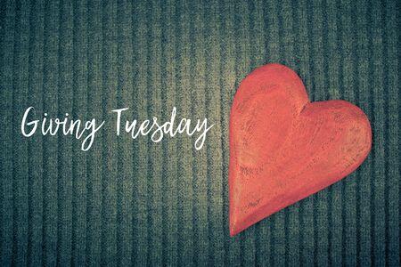 Giving Tuesday es un día global de donaciones caritativas después del día de compras del Black Friday. Caridad, dar ayuda, donaciones y concepto de apoyo con letrero de mensaje de texto y corazón de madera roja Foto de archivo