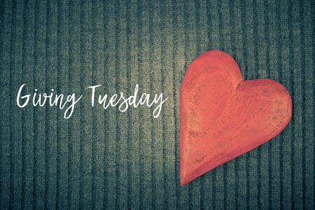 Giving Tuesday is a global day of charitable giving after Black Friday shopping day. Charity, give help, donations and support concept with text message sign and red wooden heart