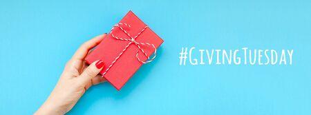 Giving Tuesday es un día global de donaciones caritativas después del día de compras del Black Friday. Caridad, dar ayuda, donaciones y concepto de apoyo con letrero de mensaje de texto y mano de mujer sosteniendo una caja de regalo roja