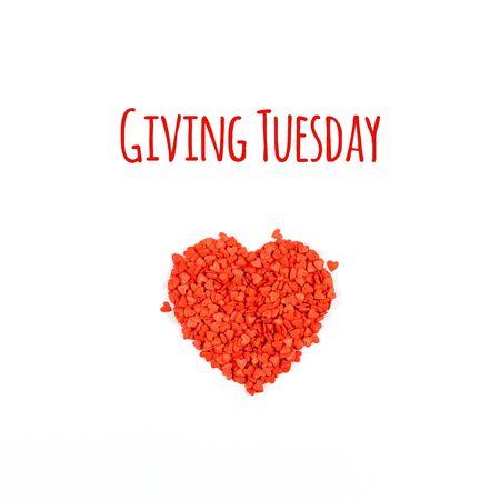 Giving Tuesday es un día global de donaciones caritativas después del día de compras del Black Friday. Caridad, dar ayuda, donaciones y concepto de apoyo con mensaje de texto y fondo blanco de confeti en forma de corazón rojo