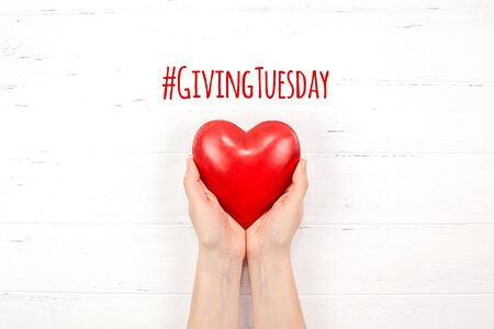 Giving Tuesday is a global day of charitable giving after Black Friday shopping day. Charity, give help, donations and support concept with text message sign and red heart in woman hands