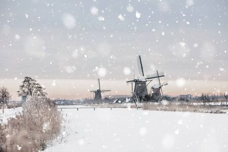 Snowy winter landscape with old rural windmills in Kinderdijk, The Netherlands. Magic background. Monochromatic neutral tones with natural light Standard-Bild