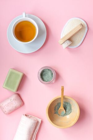 Spa, beauty cosmetics and body care treatment concept copy space. Creative top view flat lay composition bath accessories, green spirulina laminaria cleansing mask in bowl, cup of tea pink background