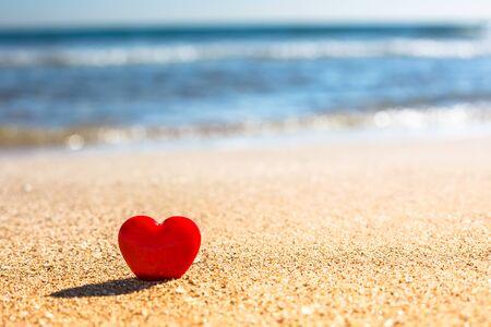 Valentijnsdag concept. Romantisch liefdessymbool van rood hart op het zandstrand met kopieerruimte. Sjabloon voor inspirerende composities en offerte ansichtkaarten. Stockfoto