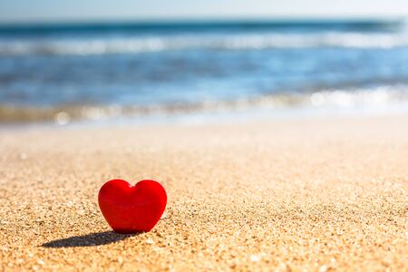 Valentines Day concept. Romantic love symbol of red heart on the sand beach with copy space. Template for Inspirational compositions and quote postcards. Banco de Imagens