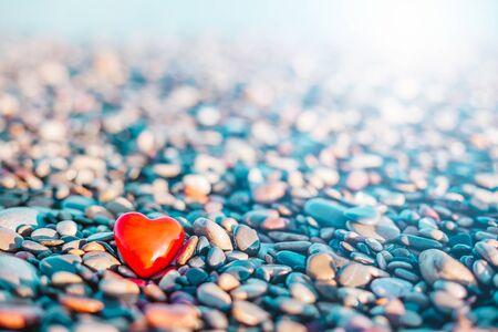 Valentinstag-Konzept. Romantisches Liebessymbol des roten Herzens am Kieselstrand mit Kopienraum. Vorlage für inspirierende Kompositionen und Zitatpostkarten. Standard-Bild
