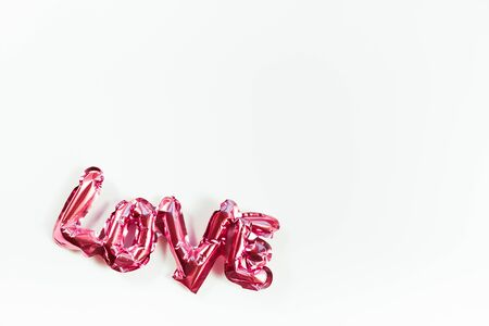 Valentines Day creative concept. Inflatable pink glossy foil balloon word sign Love with shadows isolated on white background. Top view flat lay with copy space. Light and bright composition Reklamní fotografie