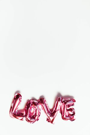 Valentines Day creative concept. Inflatable pink glossy foil balloon word sign Love with shadows isolated on white background. Top view flat lay with copy space. Light and bright composition Stock Photo