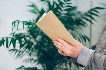 Young man reading open old paper book in the room with green plants, close up, vintage style