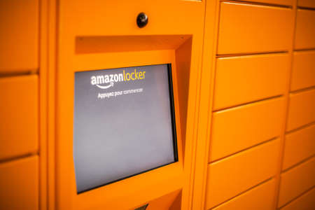 Amazon Locker in shopping mall, orange pick up point for mail order goods with Amazon brand logo on it. Screen closeup. Lyon, France - February 23, 2020