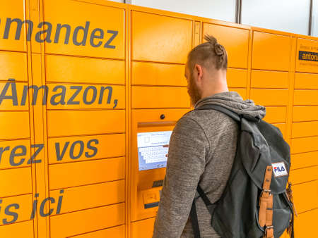 Man using Amazon Locker in shopping mall, orange pick up point for mail order goods with Amazon brand logo on it. Mobile photography. Lyon, France - February 23, 2020 Redactioneel