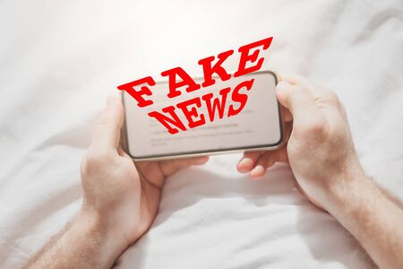 Fake news infodemics during Covid-19 pandemic concept. Man hands holding mobile phone reading global news or social net at home. Reading last news update in lockdown. Red text fake news on foreground