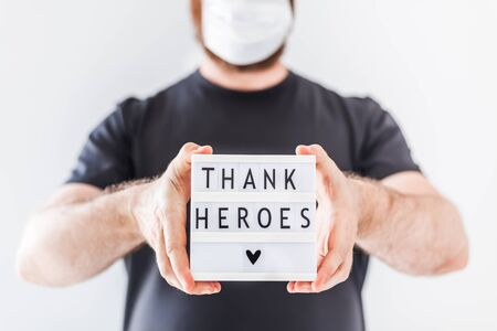 Nurse day concept. Man hands holding lightbox with Thank heroes text thanking doctors, nurses and medical staff working in hospitals during coronavirus COVID-19 pandemics.