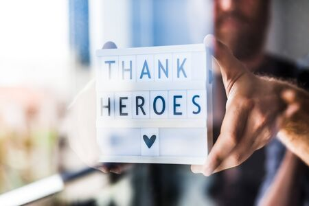 Nurse day concept. Man hands holding lightbox with Thank heroes text thanking doctors, nurses and medical staff working in hospitals during coronavirus COVID-19 pandemics. View through window glass