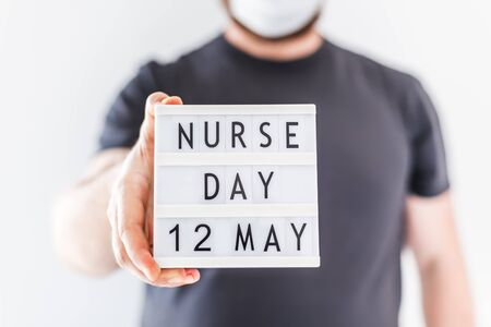 Nurse day concept. Man hands holding lightbox with text Nurse day 12 May thanking doctors, nurses and medical staff working in hospitals during coronavirus COVID-19 pandemics
