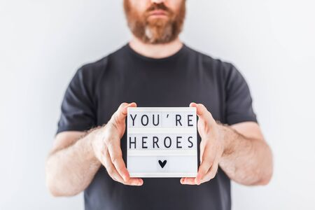 Nurse day concept. Man hands holding lightbox with You are heroes text thanking doctors, nurses and medical staff working in hospitals during coronavirus COVID-19 pandemics.