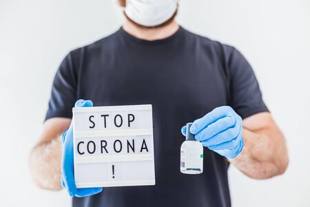 Hand sanitizer hygiene alcohol gel bottles and lightbox with text Stop Coronavirus in hands of man wearing latex medical gloves and protective mask during coronavirus COVID-19 pandemics. Healthcare