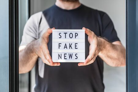 Fake news infodemics during Covid-19 pandemic concept. Man hands holding lightbox with text Stop fake news on foreground. People want to know the truth about coronavirus world spread.
