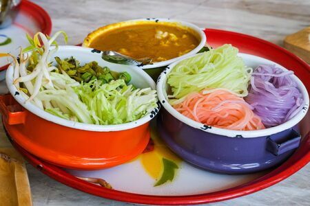 colorful of rice noddles or vermicelli crab curry sauce decorative in food carrier. vegetable slice for side dish