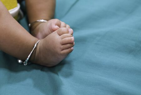 tiny toe and two leg with silver anklet sleep on soft fabric green color. Stock Photo