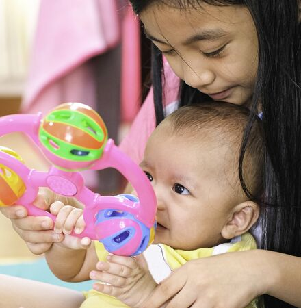 sister caucasian girl long black hair smile with baby boy and playing fun. sibling love kid in thailand family Stock Photo