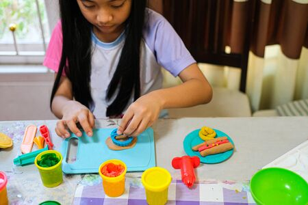 cute Thai girl black long hair playing dough mould creative and skill. colorful doh in mold.