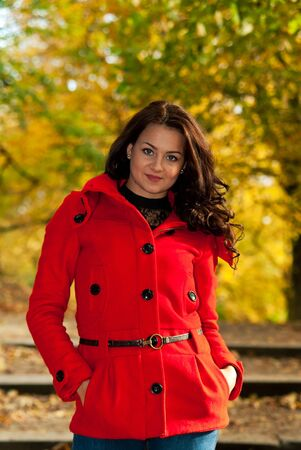 woman in red jacket on a walk in the park in the autumn afternoon photo