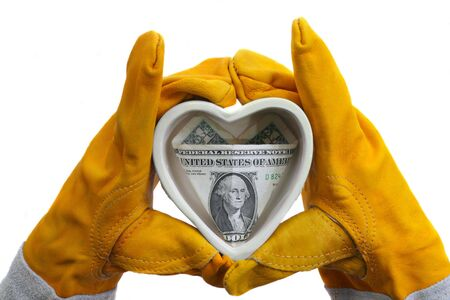 two hands in protective gloves hold ceramic heart with a dollar bill inside, isolated on white