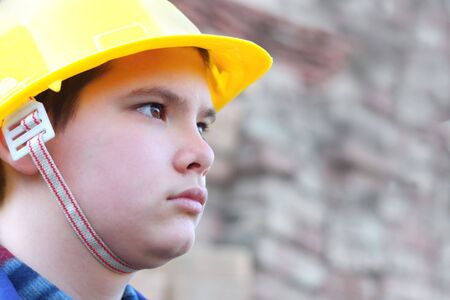 Young teenage caucasian worker with yellow helmet against the blurred brick wall. Shallow depth of field. Outside shot. Stock Photo