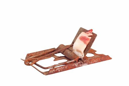 Old rusty mousetrap with bacon as a bait isolated on white
