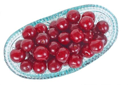 Crystal glass bowl ful of fresh cherries isolated on white