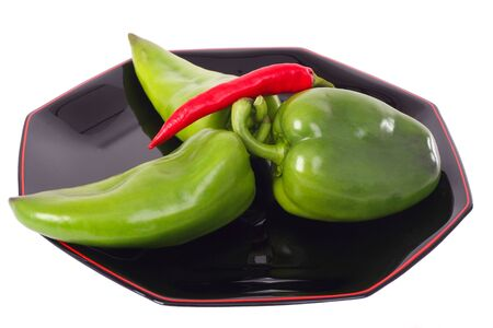 Three green peppers and red chili on the black plate isolated on white