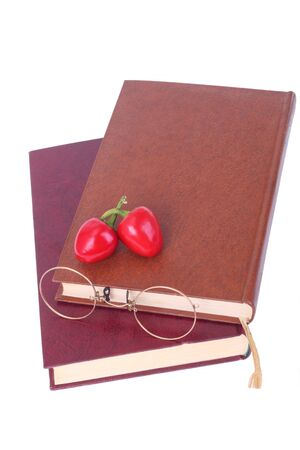 Old books, glasses and chillies isolated on white