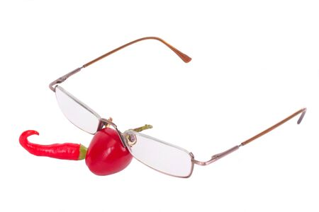 Two different red chili peppers with reading glases isolated on white