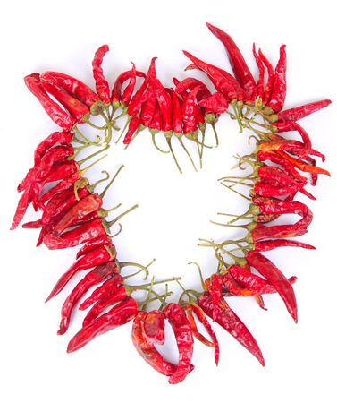 Heart shaped chaplet of dried chilies over the white background