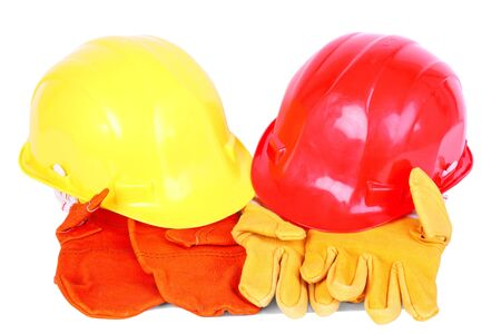 Two helmets over two pairs of protective gloves isolated on white Stock Photo