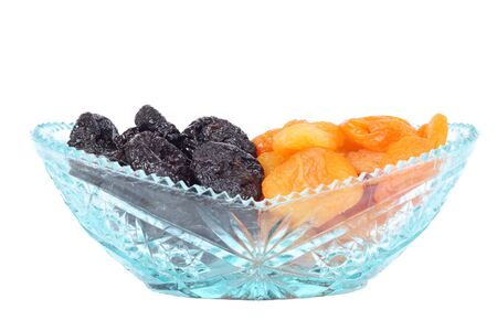 Crystal glass bowl full of dried plums and apricots isolated on white