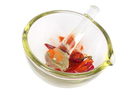 Dried red hot crumbly chili pepper in a colored glass mortar with pestle. Isolated on white.