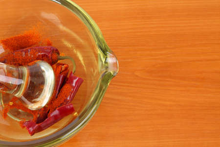 Dried red hot crumbly chili pepper in a colored glass mortar with pestle on the kitchen board.