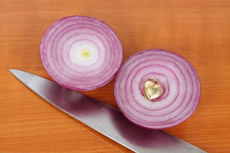 Two red onion halves, kitchen knife and golden heart on the kitchen board Stock Photo