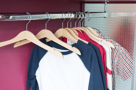 closet rod: wood hangers with kid cloths Stock Photo