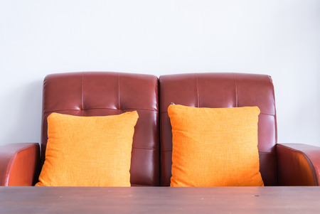 red leather sofa with orange pillows photo